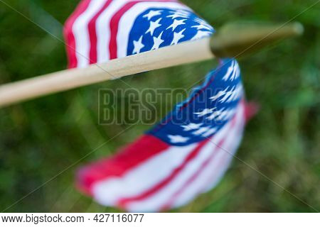 A small American flag rests in front of a fallen hero at a military cemetery