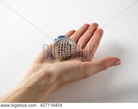 A Used Aluminum Coffee Capsule Is Placed In The Man's Open Palm. Wooden Background. The Concept Of R