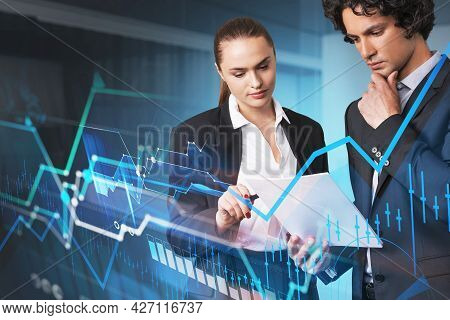 Businessman And Businesswoman Looking Into Notes. Stock Market Graph Changes, Candlesticks And Finan