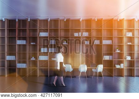 Motion Blurred Woman In Formal Wear Is Walking Along Modern Common Space With Bookshelves And Workpl
