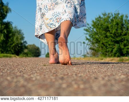 A Woman Dressed In A Dress Walks Barefoot On The Asphalt. Rear View. The Concept Of Travel, Recreati