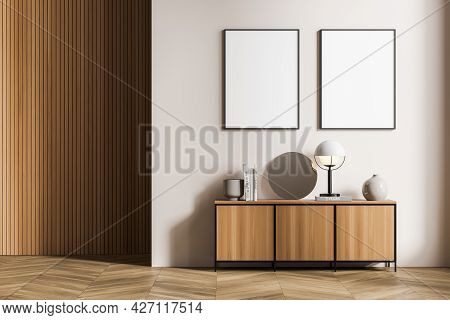 Two White Posters In Beige Living Room Interior. Sideboard With Interior Items. Wall With Wooden Coa