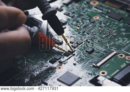 Technician Checking Laptop Circuit Board With Multimeter Probe