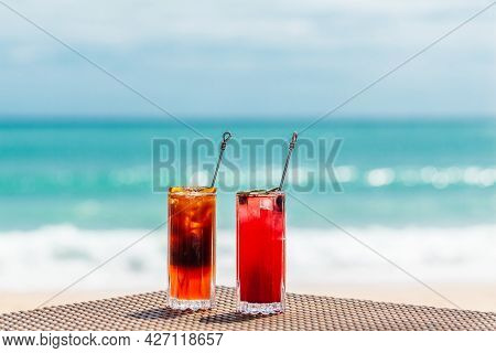 Fresh Exotic Colorful Cocktails On Table By Sea, Relaxing Holidays In Paradise Concept. Iced Raspber
