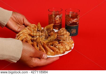 Close-up Of Hands Serving A Plate Of Delicious Oriental Traditional Moroccan Sweet Dessert And Mint