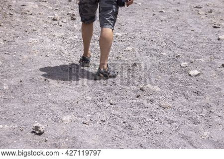Tourist In Sandals Walking Along The Footpath To The Top Of Vesuvius Volcano On A Hot Day, Mount Ves