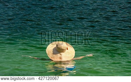 A Bright Wide-brimmed Hat On A Woman In Clear Emerald Water.