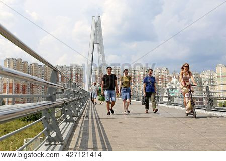 Moscow, Russia - July 2021: People Walking On The Pavshinsky Pedestrian Bridge In Summer Above The M