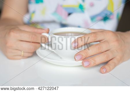 The Concept Of Self-care, Beauty. Women's Hands With A Neat Manicure Of Nude Color. Fingers With Pin