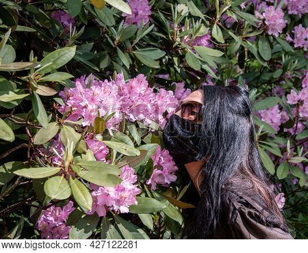 A Girl In A Mask And Glasses Sniffs Flowers. Allergy Concept, Seasonal Allergic Rhinitis.