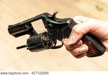 A Hand Holds A Revolver With One Cartridge In The Drum On A Blurred Background.