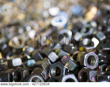 A Lot Of Hexagonal Nuts. Mechanical Fasteners With A Threaded Hole, Close Up