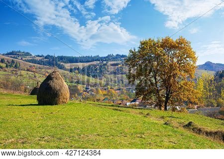 Tree And Haystack In Fall Foliage On The Hill. Autumnal Rural Scenery On A Sunny Day. Village In The