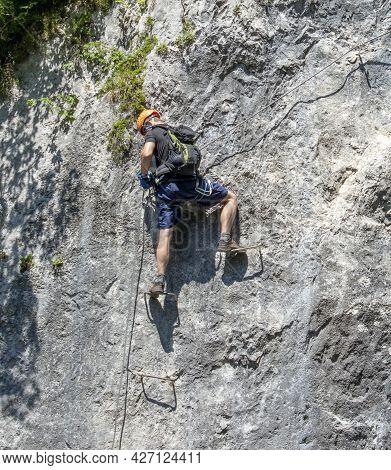 Unrecognizable Young Man Climbing Via Ferrata In Julian Alps. Slovenia.