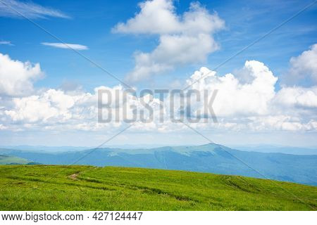 Idyllic Summer Landscape. Grassy Meadow And High Peak In The Distance. Sunny Weather With Fluffy Clo