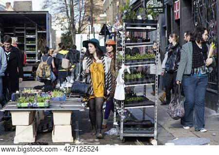 London, England - October 12, 2018 People Buying Flowers At Columbia Road Flower Market. Two Brightl