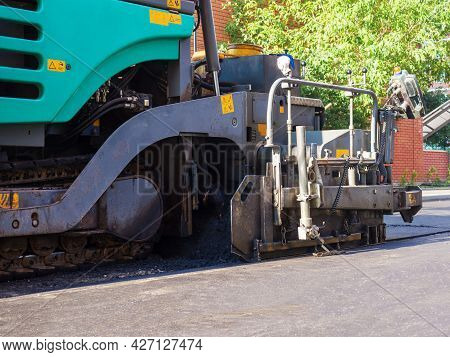 Close-up Side View Of An Road Paver In The Process Of Paving Asphalt.