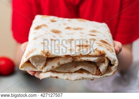 Freshly Baked Lavash In A Close-up In The Hands Of A Girl