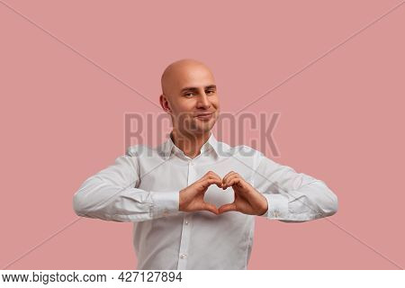 Wholeheartedly. Happy Bald Man With Bristle In White Shirt, Holds Fingers In Heart Gesture. Shows Hi