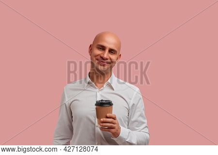 Joyful Smiling Bald Man With Bristle Holds Paper Takeaway Cup, Enjoys Aromatic Beverage At Work With