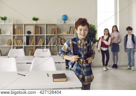 Smiling Caucasian Schoolboy With Backpack Stand Next To Desk Posing For Camera