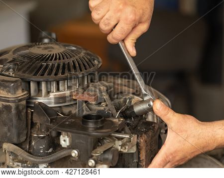 A Man Repairs The Engine Of A Gasoline Lawn Mower. Close-up Hands Holding Wrench