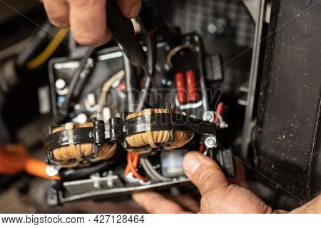 Close-up. The Hands Of A Working Electrician In The Process Of Repairing An Electric Generator In A