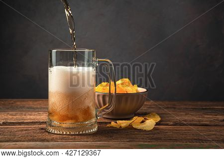 Pouring Beer Into A Beer Glass On The Background Of Potato Chips. Side View, Space For Copying.