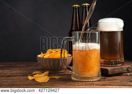 Two Glasses Of Beer, Chips And Beer Bottles On A Brown Background. Side View, Space For Copying.