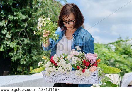 Female Florist Doing Floral Arrangement Outdoors. Flower Basket Creation Workflow