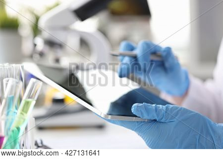 Scientist Chemist Enters Results Of Research Into Tablet Closeup