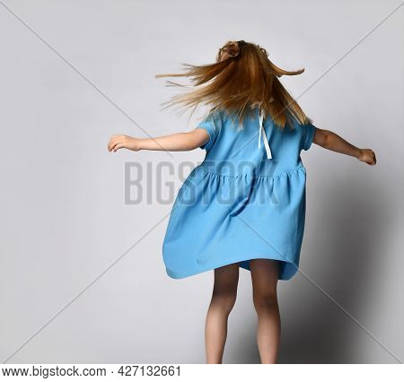 Unrecognizable Little Blonde Girl Dances And Whirls On A White Background. Back View Of A Child In A