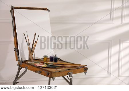 Easel With Blank Canvas, Palette And Brushes In Art Studio. Space For Text