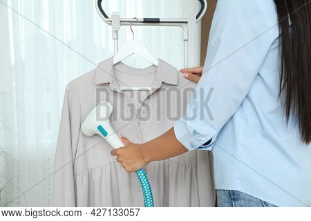 Woman Steaming Blouse On Hanger At Home, Closeup