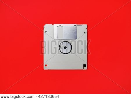 Gray Diskette On Red Paper Background. Floppy Disc. Flat Lay.