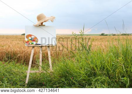 Wooden Easel With Blank Canvas, Painting Equipment And Hat In Field. Space For Text