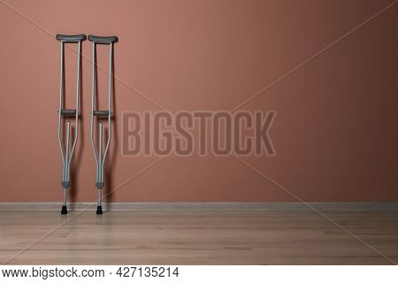 Pair Of Axillary Crutches Near Pale Pink Wall. Space For Text