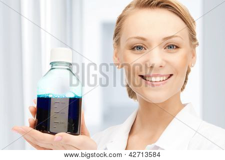 female lab worker holding up bottle with blue liquid
