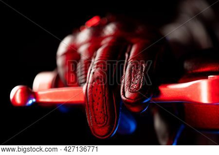 Motorcyclist Hand In Leather Glove Presses Brake Lever Under City Lights At Night. Culture And Aesth