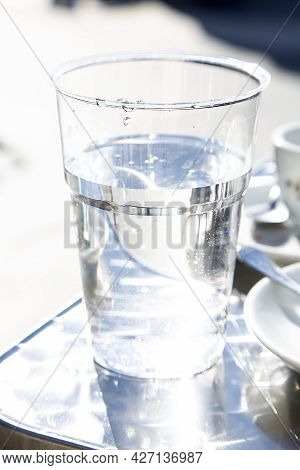 Transparent Plastic Glass With Non Alcoholic Liquid On Metal Table In Outdoor Bar. Drinking Water Pr