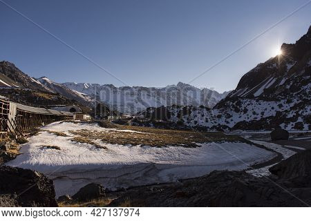 Mountain Landscape With Snow In Andes With Sun In The Horizon And An Old Train Line Not In Use. Las