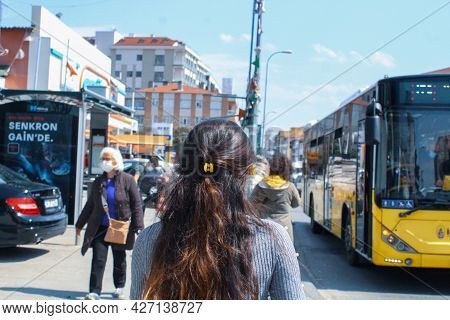 Maltepe, Istanbul, Turkey - 04.15.2021: A Young Brunette Woman With Mask Walking Towards The Bus Sta