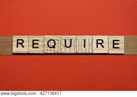 Text The Word Require From Gray Wooden Small Letters With Black Font On An Red Table