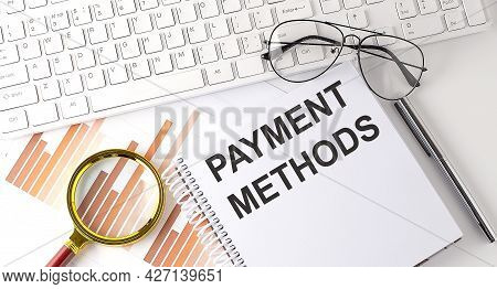 Payment Methods Text Written On Notebook With Keyboard, Chart,and Glasses