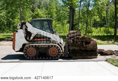 A Compact Front Loader And A Pallet With Rolls Of Sod Grass For Installation At A New Home Construct