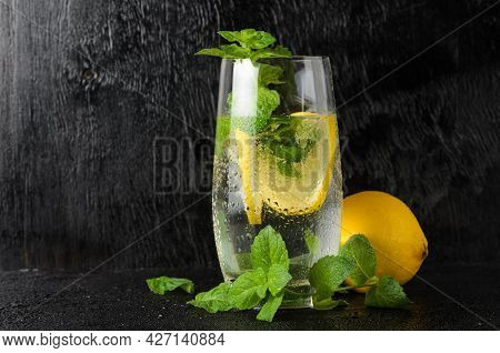 A Large Glass Of Water With Lemon, Mint Leaves And Ice, Covered With Water Droplets. A Glass Of Lemo