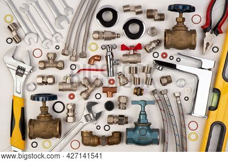 Plumber tools and spare parts on white wooden background, top view, flat lay