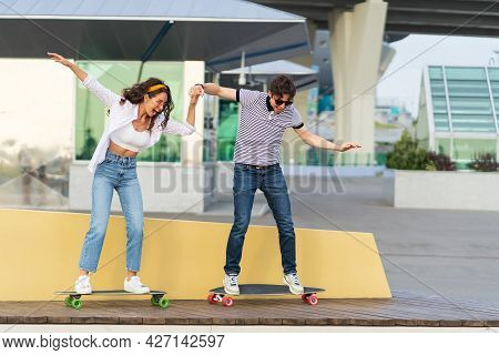 Active Boyfriend And Girlfriend Learn To Ride Longboard Together Holding Hands. Playful Young Couple