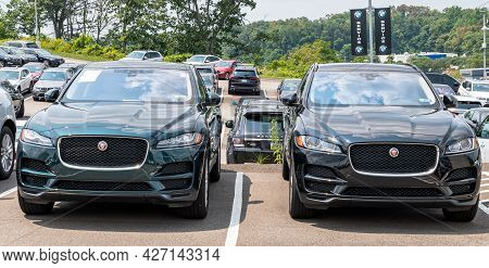 Monroeville, Pennsylvania, Usa July 18, 2021 A Green And A Black Jaguar Suvs Parked Together In A Pa