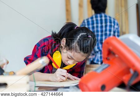 Children Learning Woodworking In The Craftsman Workshop, Teenager Boy With His Little Sister Buildin